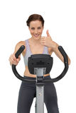 Beautiful woman gesturing thumbs up on stationary bike Stock Photos