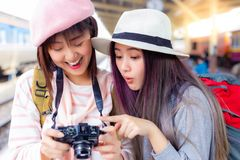 Beautiful woman get excited when tourist woman see wonderful photo at camera and saying wow that makes her friend laugh. stock images