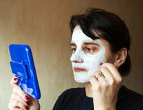 Beautiful woman gets cosmetic mask in the mirror Royalty Free Stock Image