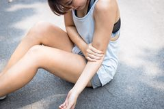 A beautiful woman gets hurt, injure, painful at her arm. Charming beautiful girl has bruise on her arm. Pretty asian girl is royalty free stock image