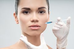 Beautiful woman gets injection in her face Stock Images
