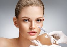 Beautiful woman getting cosmetic injection in eye area from beautician. Clean Beauty concept Stock Images