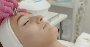 Beautiful woman is getting the diamond microdermabrasion and facial peeling procedure in beauty salon. Skincare and. Health. 4k footage stock footage