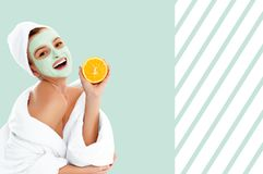 Beautiful woman with clay mask on pastel green background. Beauty and spa Stock Image