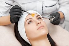 Beautiful woman getting facial peeling mask in beauty salon. stock photo