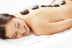 Beautiful Woman Getting Hot Stone Massage in Spa Salon. Royalty Free Stock Photos