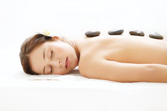 Beautiful Woman Getting Hot Stone Massage in Spa Salon. Beauty t. Reatment Stock Photo