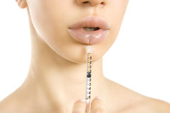 Beautiful woman getting an injection in her lips. Royalty Free Stock Photography