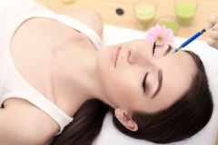Beautiful woman getting lifting injection in forehead. Close-up woman hyaluronic acid injection. injections of skin rejuvenation. Royalty Free Stock Image