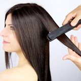 Beautiful woman getting long silky hair straightened by hairstylist Stock Photography