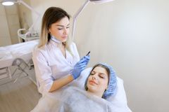 Beautiful woman getting makeup by eyebrow tattoo pen by cosmetologist. Gorgeous female person getting makeup by eyebrow tattoo pen by cosmetologist. Concept of royalty free stock image