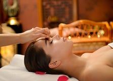Beautiful woman getting spa treatment. Young attractive girl having facial massage at spa resort Royalty Free Stock Image