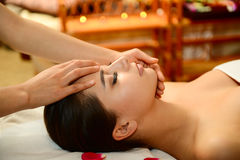 Beautiful woman getting spa treatment. Young attractive girl having head massage at spa resort Royalty Free Stock Images
