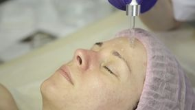 Beautiful woman getting a Treatment of facial skin. Beautician doing face cleaning on a beautiful girl face, cleaning