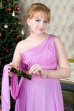 Beautiful woman with gift box. Portrait of the Beautiful woman with gift box at the Christmas tree Stock Photography