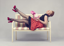 Beautiful woman with gift box in hands. Laughing while sitting on a sofa in a retro style Stock Photos