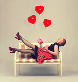 Beautiful woman with gift box. In hands laughing while sitting on a sofa in a retro style Royalty Free Stock Image