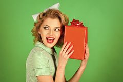 Beautiful woman with gift box in hands smiling. In a retro style Royalty Free Stock Image