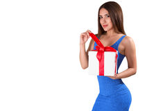 A beautiful woman, with gift box, isolated on white. A slender woman in a blue dress. Holiday concept. Woman opens a gift. Copy space Royalty Free Stock Photography