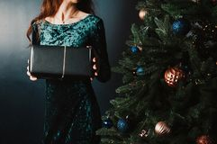 Beautiful woman with gift box near Christmas tree stock photo
