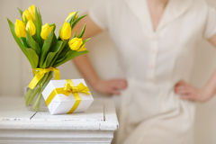 Beautiful woman with a gift and fresh yellow tulips. Royalty Free Stock Photography