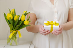 Beautiful woman with a gift and fresh yellow tulips. Royalty Free Stock Photo