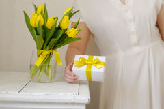 Beautiful woman with a gift and fresh yellow tulips. Royalty Free Stock Images
