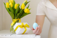 Beautiful woman with a gift and fresh yellow tulips. Easter. Royalty Free Stock Images