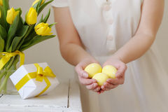 Beautiful woman with a gift and fresh yellow tulips. Easter. Royalty Free Stock Image