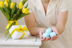 Beautiful woman with a gift and fresh yellow tulips. Easter. Stock Photo