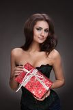 Beautiful woman with gift on grey. Portrait of brunette beautiful woman with gift on grey Royalty Free Stock Photography