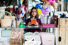 Beautiful woman gift seller in a mall. Young beautiful woman gift seller in a mall is smiling and giving a present to the camera Royalty Free Stock Photography