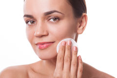Beautiful woman girl cleansing her face with cotton pad fiber Stock Photo