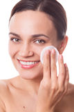 Beautiful woman girl cleansing her face with cotton pad fiber Stock Image
