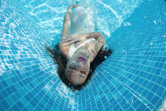 Beautiful woman girl dress underwater diving swim blue sunny day pool Stock Photos