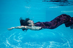 Beautiful woman girl dress underwater diving swim blue sunny day pool Royalty Free Stock Photography