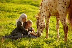 Beautiful woman and girl embracing horse stock photo