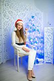 Woman new year. Beautiful woman girl lady seating on white chair, Christmas time. With colorful lights from Christmas tree, pattern on background, selective Royalty Free Stock Photo