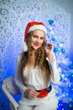Woman new year. Beautiful woman girl lady seating on white chair, Christmas time. With colorful lights from Christmas tree, pattern on background, selective Royalty Free Stock Photos