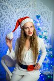 Woman new year. Beautiful woman girl lady seating on white chair, Christmas time. With colorful lights from Christmas tree, pattern on background, selective Stock Photography