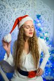 Woman new year. Beautiful woman girl lady seating on white chair, Christmas time. With colorful lights from Christmas tree, pattern on background, selective Royalty Free Stock Images
