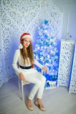 Woman new year. Beautiful woman girl lady seating on white chair, Christmas time. With colorful lights from Christmas tree, pattern on background, selective Stock Photos