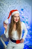 Woman new year. Beautiful woman girl lady seating on white chair, Christmas time. With colorful lights from Christmas tree, pattern on background, selective Stock Image