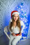 Woman new year. Beautiful woman girl lady seating on white chair, Christmas time. With colorful lights from Christmas tree, pattern on background, selective Stock Photo