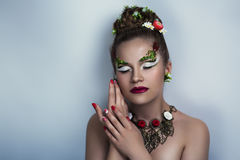 Beautiful woman. Girl with beautiful makeup, hair and nails. Floral decorations for jewelry. Hands with red nails, neat manicure. Dreaming, thinking, love nature Royalty Free Stock Image