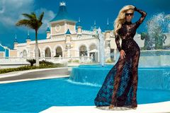 Beautiful woman in an elegant evening gown, stands against the background of a fountain in the Caribbean. Beautiful woman girl model in an elegant evening gown royalty free stock images
