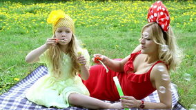 Beautiful woman and girl outdoors blowing bubbles, lying in the grass stock footage