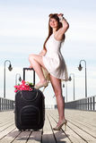 Beautiful woman girl sea mooring suitcase on a pier Stock Image