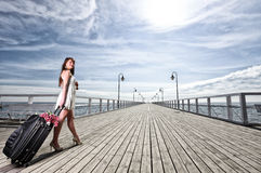 Beautiful woman girl sea mooring suitcase on a pier Stock Images