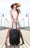 Beautiful woman girl sea mooring suitcase on a pier Royalty Free Stock Photography